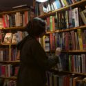 A woman browses full bookshelves