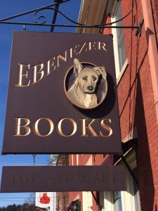 a wood cut sign with a dog's head and the text ebenezer books