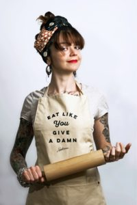 Cecilia Granata wearing an Eat Like You Give a Damn apron and holding a rolling pin