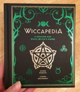 Black hardcover book with green occult designs and symbols