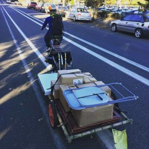 Elly rides a bike through Portland with a trailer full of book boxes and event stuff.