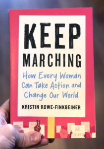 The cover of Keep Marching, which is the title on a protest sign on a pink background. Along the bottom are more protest signs and hands reaching up.