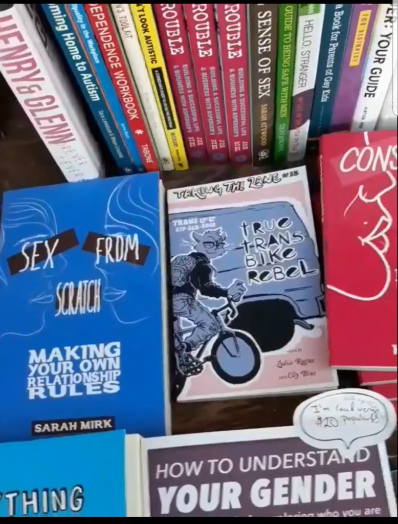 """photograph of books on display, """"True Trans Bike Rebel"""" at the center"""