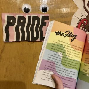 googly-eyes over a note with the word PRIDE and a page from This is San Francisco about the PRIDE Flag