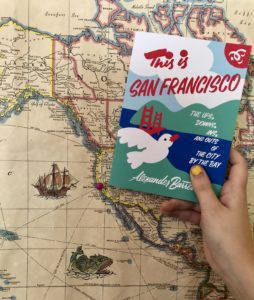 This is San Francisco book held in front of a map of North America, with a pin on San Francisco