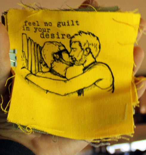 "patch with image of two men kissing and the text ""feel no guilt in your desire"""