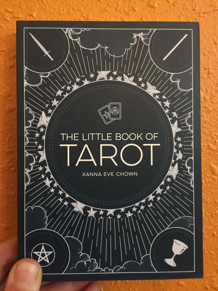 Navy blue cover with white detailing and the four signs of the tarot