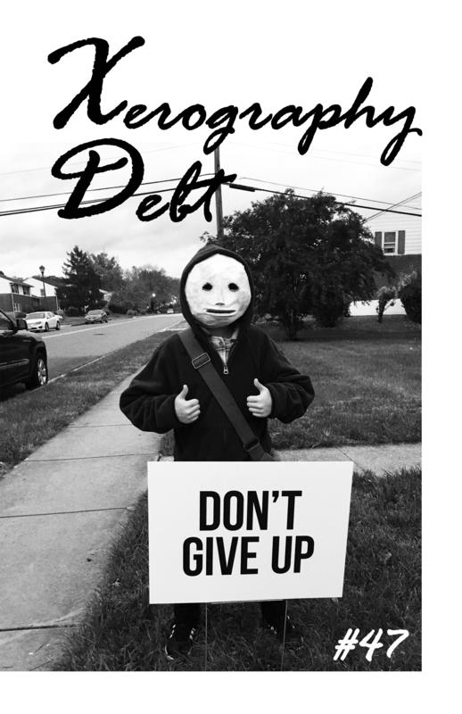 "A person in a clay mask standing behind a sign that reads ""DON'T GIVE UP."""