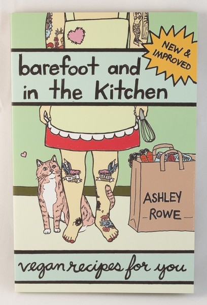 A book with an illustration of a barefoot person with tattoos in an apron and a cat at their feet