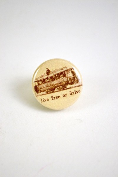 Button with an illustration of historical cyclists and the words Live Free or Drive