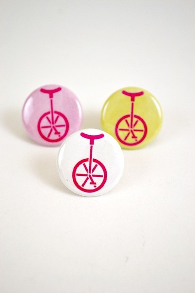 a one inch button with an illustration of a unicycle