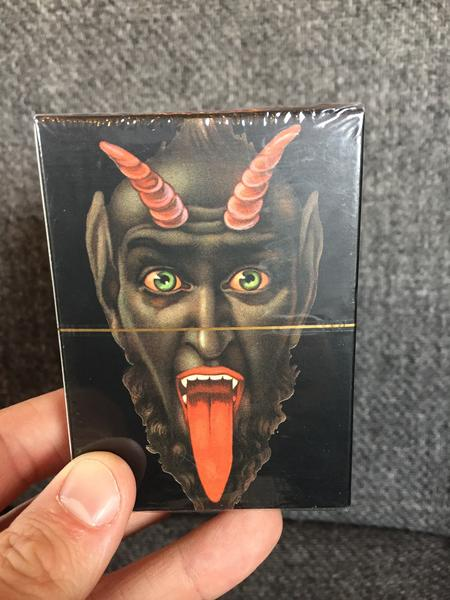 Krampus Playing Cards: 52 Vintage Designs by Monte Beauchamp (An illustration of a dark and evil looking Krampus with horns, bulging eyes, a long, red tongue, and fangs)
