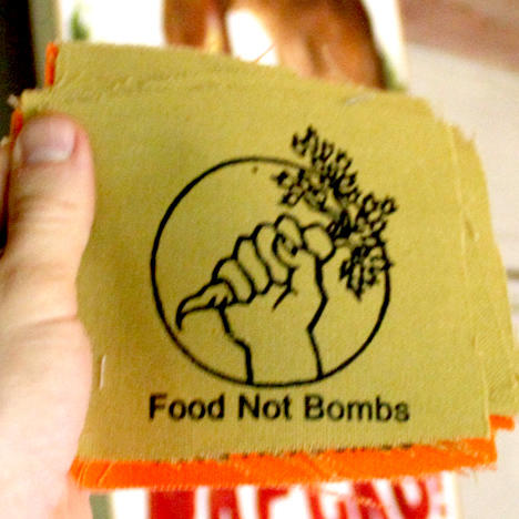 A hand holding a carrot with the text Food not Bombs printed on a canvas patch