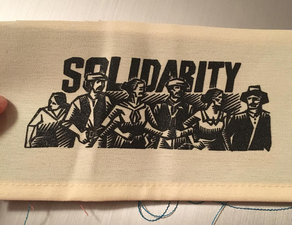 bold text with a woodcut drawing of a crowd of people hugging