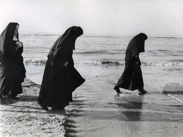 a vintage photo of three nuns wading into a body of water