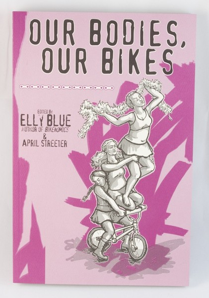 A pink book with an illustration of three women riding the same bike, holding each other together
