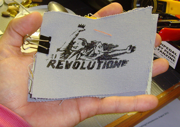 "patch with people cheering that says ""revolution"""